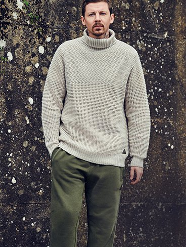 Professor Green stands with one hand in pocket wearing cream ribbed turtleneck and khaki trousers.