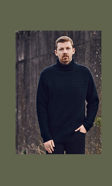 Professor Green stands with one hand in pocket wearing navy ribbed turtleneck and black trousers.