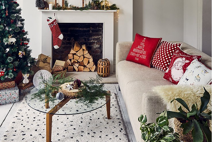 Cream sofa with assortment of red and white Christmas scatter cushions and cream faux fur throw next to fireplace with hanging stocking, Christmas tree and presents.