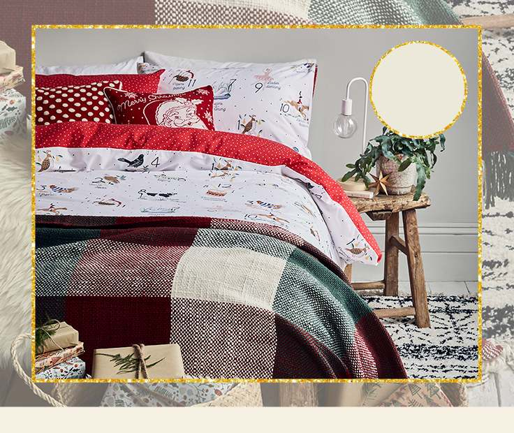 Double bed with wooden side table, white lamp and plant with 12 days of Christmas reversible duvet set, check print throw and wrapped presents at the bottom of the bed.