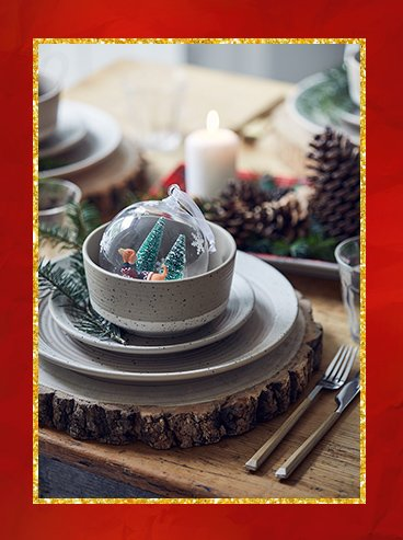 Natural speckled dinner setting with Disney bauble placed inside the dish next to tartan sharing platter with candle and pinecone.