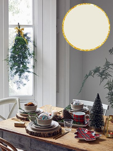 Wooden table with natural speckled 12-piece dinner setting surrounded by Christmas tree decorations, tartan printed sharing platter, mug, Christmas tree-shaped tray and candle with large window with Christmas tree decoration in the background.
