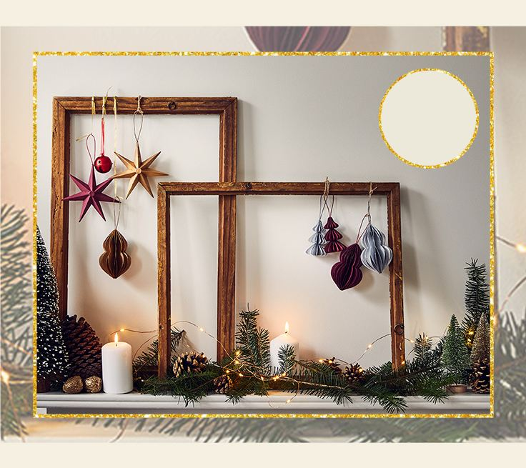 Two empty wooden frames with red, gold and silver decorations placed on white ledge with candles, Christmas tree decorations, pinecones, and warm white fairy lights.