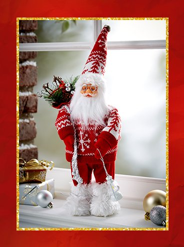 Santa decoration wearing red and white Fair Isle outfit, and white faux fur snow boots carrying a festive bouquet and lantern surrounded by baubles and wrapped presents.