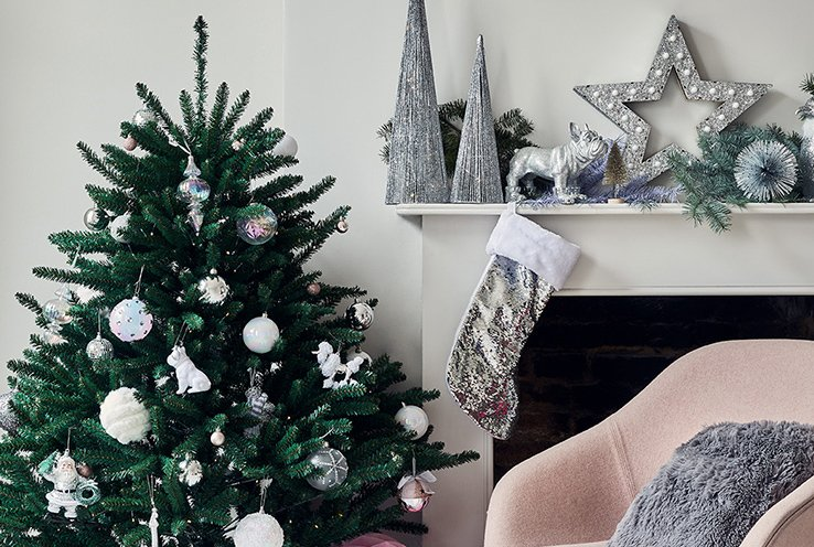 Christmas tree with silver and gold decorations next to white fireplace with silver decorations and silver stocking with a light pink chair and grey cushion.