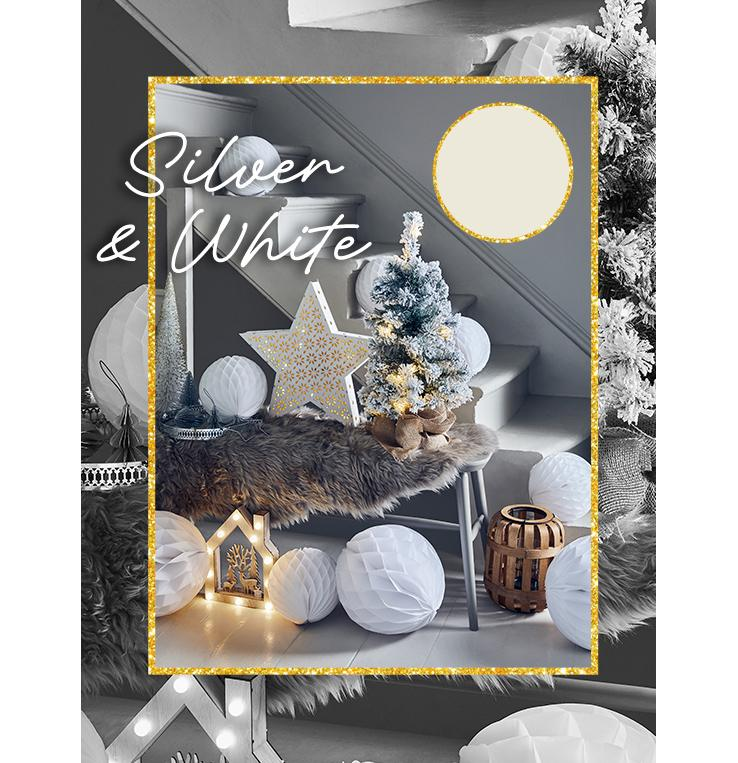 Grey table topped with a brown faux fur rug with white paper pom-pom decorations, light-up reindeer house, light-up white star and Christmas tree all in front of a white staircase.