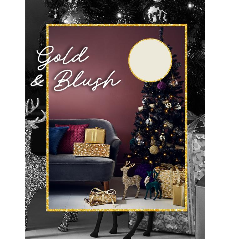 Black pre-lit Christmas tree with multi-coloured decorations, gold presents and glittery reindeer decorations next to grey sofa with red cushion, blue cushion and two gold presents.