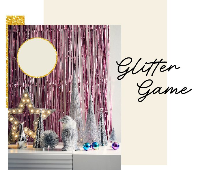 White surface with glitter silver penguin, plain silver penguin, silver and glitter Christmas tree decorations, multi-coloured baubles and silver light-up wooden star with pink and silver hanging tassel wall decoration in the background.