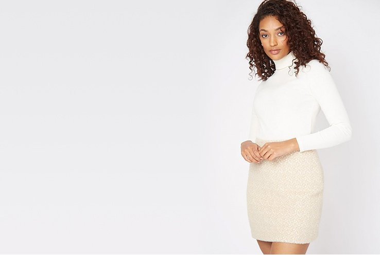 Woman with curly brown hair poses wearing white roll-neck top and nude mini skirt.