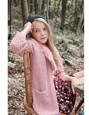 Girl sitting on a chair in the woods wearing a pink knitted cardigan