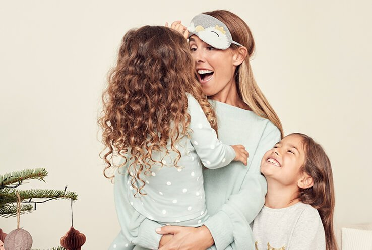 A woman with two little girls wearing light blue and cream pyjamas.