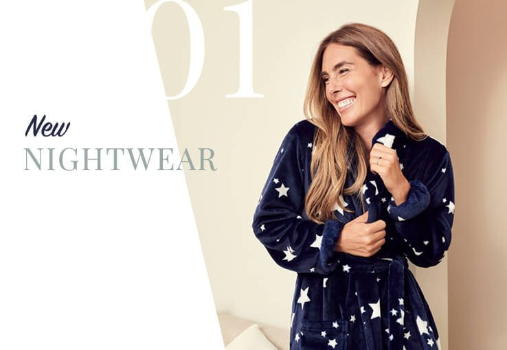 A smiling woman wearing a navy starry pyjama set.