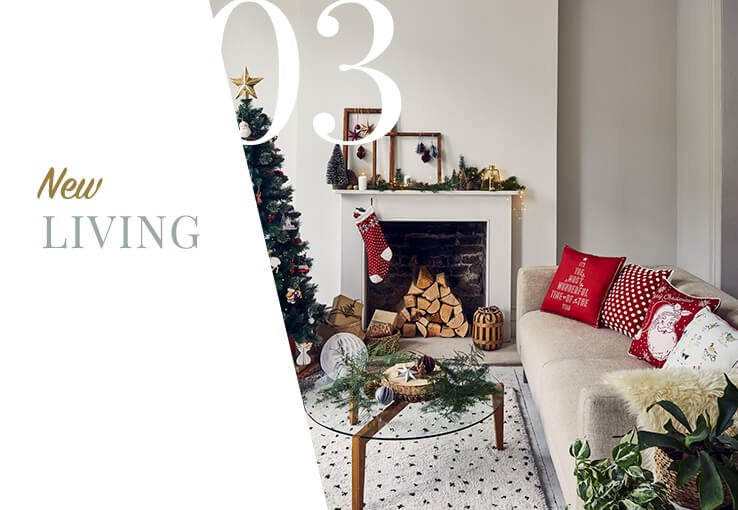 Cream sofa with assortment of red and white Christmas scatter cushions and cream faux fur throw next to fireplace with hanging stocking and festive decorations.