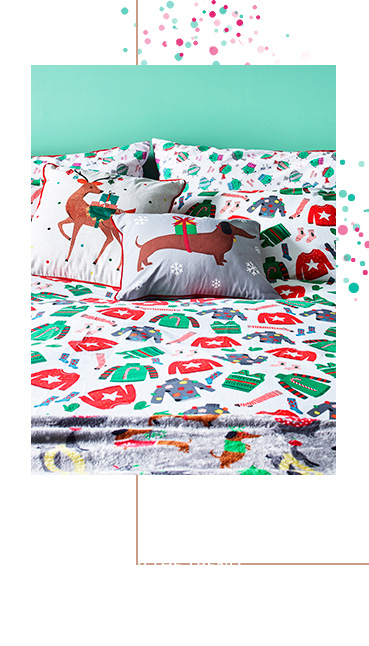 Bed with Christmas jumper bedding and cushions with a sausage dog and reindeer