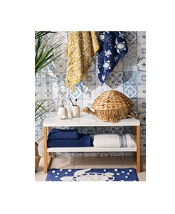White table topped with cream turtle tumbler set, turtle wicker basket and navy and cream towels.