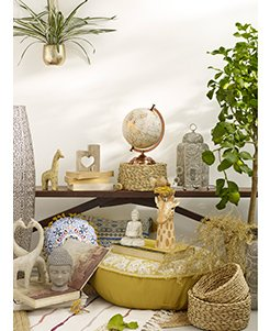 Brown wooden table surrounded by assorted scatter cushions, wicker accessories, artificial plants and buddha and giraffe ornaments.