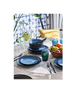 Clear table with blue reactive glaze dinner set, fruit bowl and blue textured tumblers.