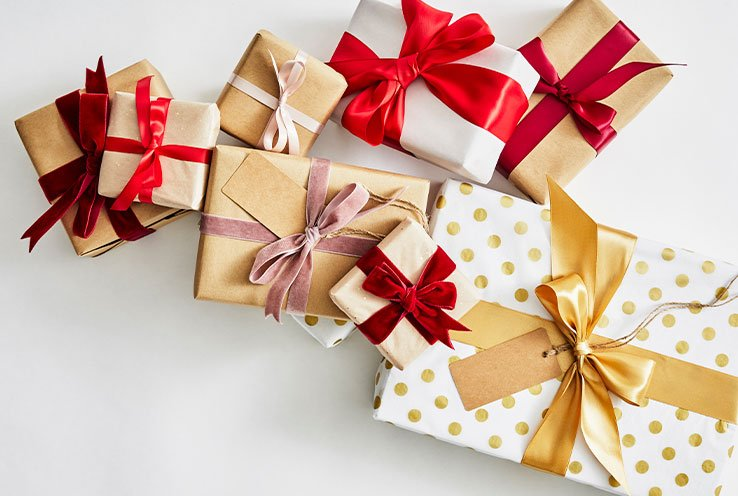 A selection of present boxes wrapped with brown, white and gold polka dot wrapping paper and tied with red and gold ribbon.