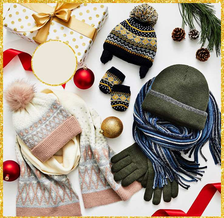 A selection of winter hats, scarves and gloves on a white background surrounded by red and gold baubles and festive ribbon.
