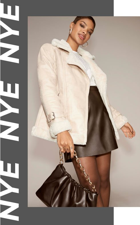 Woman with short brunette hair poses wearing white top with diamante detailing, brown PU A-line skirt, brown PU handbag with gold-stone strap, brown tights and cream coat with faux fur trims.