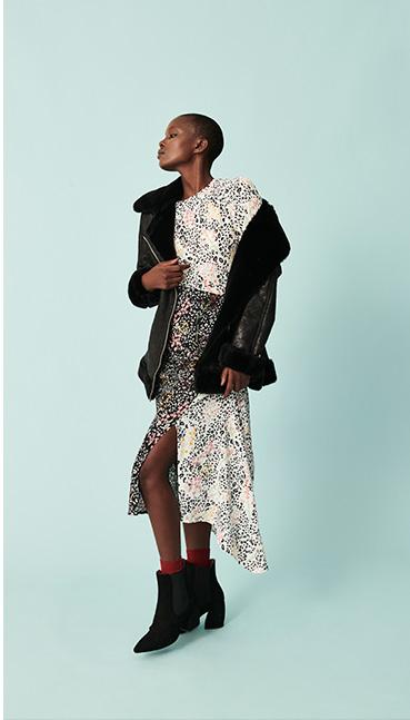 Woman in black faux fur trim biker jacket over floral midi dress and black boots