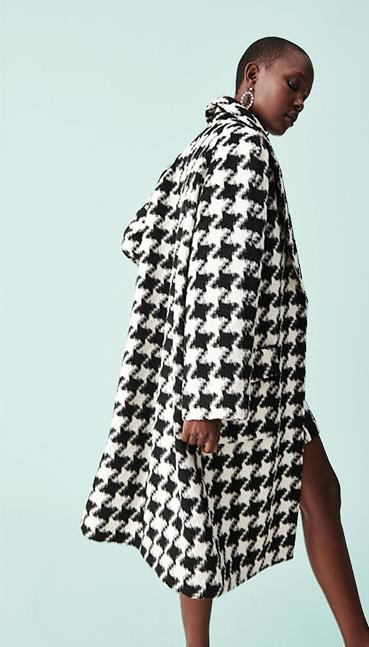Woman wearing black and white longline jacket
