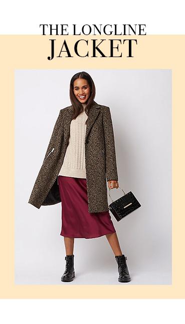 Woman carrying a black handbag wearing a leopard print formal coat over a beige jumper, burgundy skirt and black boots