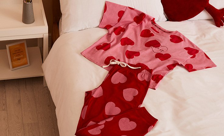 Pink and red heart print pj t-shirt and trousers set laid on white bedding with red heart shaped cushion.