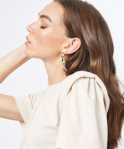 Side profile of brunette woman with eyes closed raising one hand to her face wearing blush padded shoulder longline tunic top.