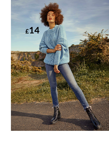 Woman in field wearing blue cable jumper, jeans and black boots
