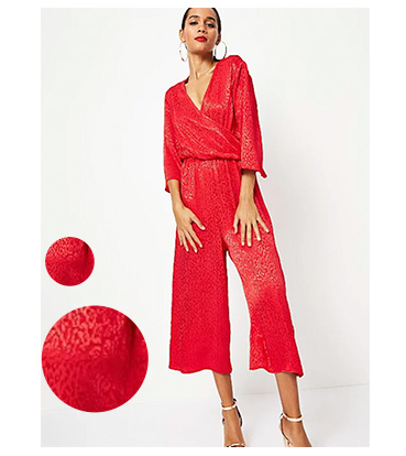 This red culotte jumpsuit comes in metallic leopard print with flared sleeves and a wrap-style front