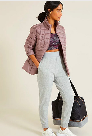 Woman holding a bag wearing a pink jacket over a sports bra, grey joggers and white trainers