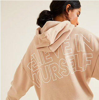 Woman facing away wearing a beige 'Believe in yourself' slogan hoodie