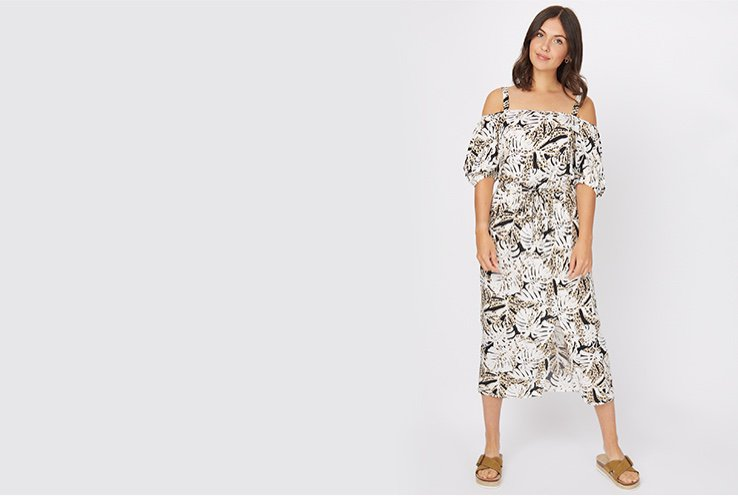 Woman wearing a white tropical leaf print cold shoulder midi dress with tan sandals