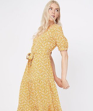 Woman wearing an ochre ditzy floral tiered midi dress with leopard print sandals