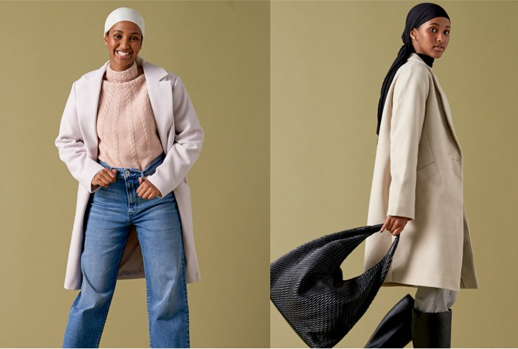 One woman wearing a lilac longline formal coat with a pink jumper, jeans and white headscarf, and a second woman turned to the side wearing a beige longline formal coat over grey trousers, black knee-high boots and a black headscarf and holding a large black bag