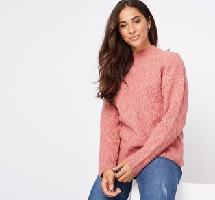 Woman sitting on a white box wearing a pink diamond knit jumper and distressed jeans