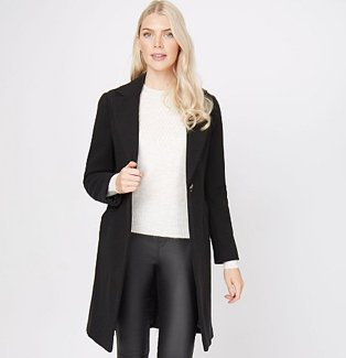 Woman wearing a black longline formal coat with a white top and black jeans