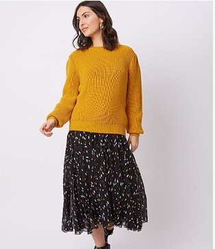 Woman wearing a mustard yellow pleated sleeve jumper with a black terrazzo patterned skirt