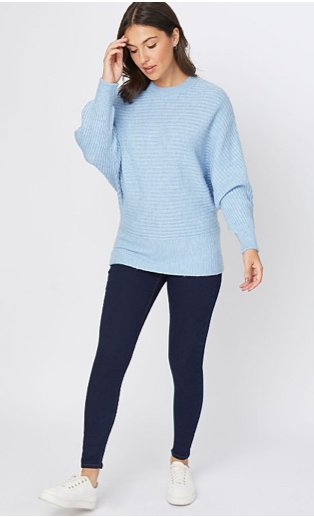 Woman wearing Wonderfit dark wash skinny jeans, white trainers and a pale blue ribbed batwing jumper