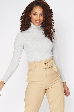 Woman wearing a grey turtle neck top with camel belted cropped trousers