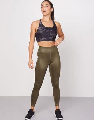 A woman wearing khaki high shine leggings with a black camo sports bra.