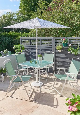 Sunny garden features miami 6 piece flower lab patio set with greenery in the background.