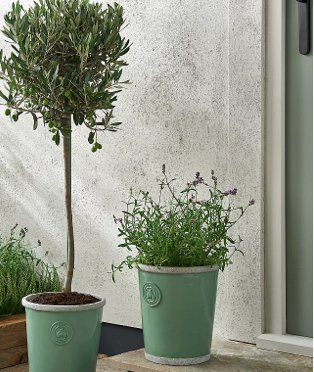 Two green 'bee happy' planters outside green front door with textured wall in background.