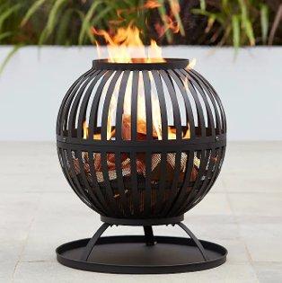Black Expert Grill log burner lit on patio in garden.