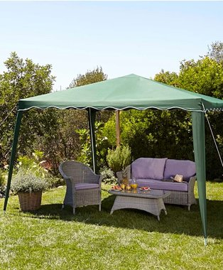 Large green gazebo shelters a natural wicker garden sofa with purple seat cushions and table topped with fruit and iced drinks in sunny garden.