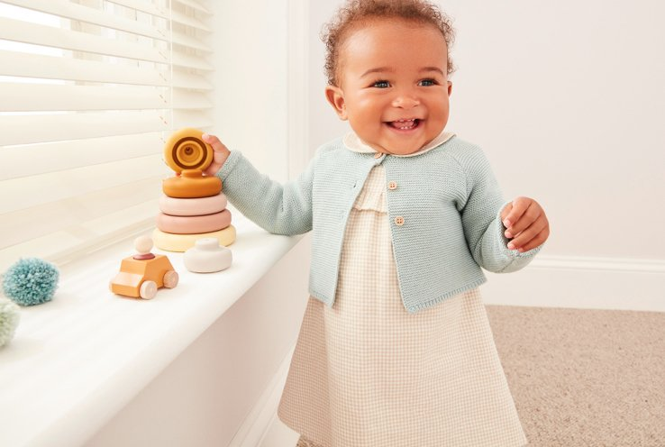 Smiling baby wearing turquoise cardigan over a cream knitted dress standing by a window stacking wooden hoops.