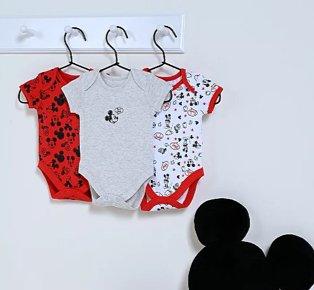 3 Disney Mickey Mouse bodysuits hanging from white hooks with black Mickey Mouse cushion below.