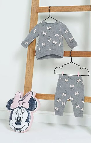 Disney Minnie Mouse grey sweatshirt and joggers outfit hanging from wooden ladder with pink Minnie Mouse cushion below.