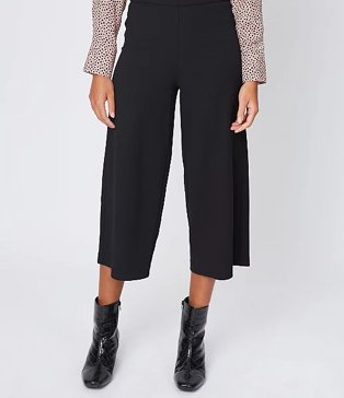 Close up of woman wearing black ponte culottes and black glossy boots.